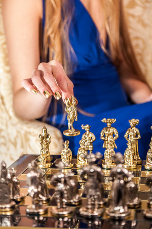 minx: Play chess. Female hand with elegant gold manicure holding chess piece. Stock Photo