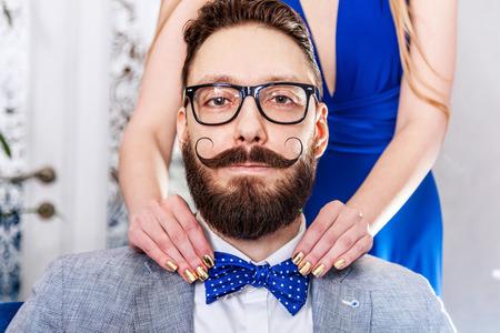 manicura: Mujer con la manicura endereza una corbata de lazo para hombre pasado de moda en gafas con una barba y un bigote rizado. Foto tonos sepia, estilizado rodaje retro.