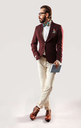 male models: Portrait of beautiful stylish young bearded man in a burgundy jacket and bow tie with book in hand