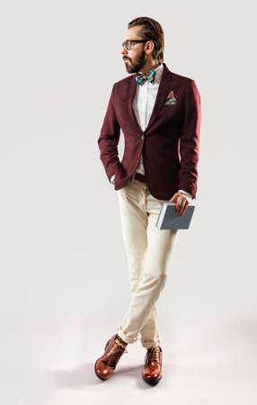 modelos hombres: Retrato de la hermosa joven barbudo elegante con una chaqueta de color burdeos y pajarita con el libro en la mano