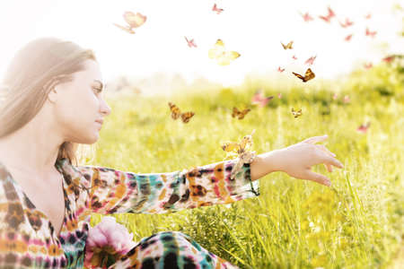 femme papillon: humeur d'été. Fille assise dans une prairie dans un essaim de papillons voletant. Banque d'images