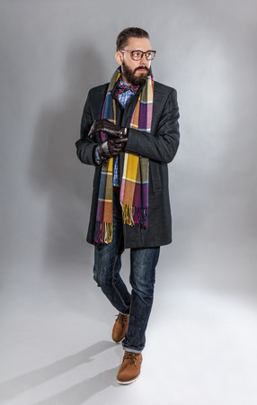 checkered scarf: Fashionable handsome stylish bearded man in coat and in a checkered scarf and bow tie. Stock Photo