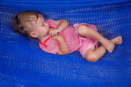 professionally: Little baby girl asleep outdoors on a hammock All my images are professionally retouched. Stock Photo