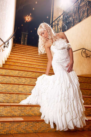 beautiful cinderella: Beautiful blond girl in a wedding dress going down the stairs