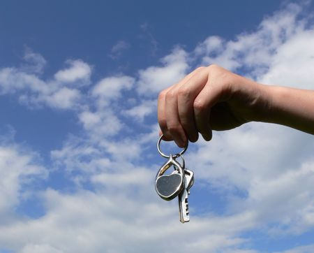 Hand and keys on blue sky with clouds photo