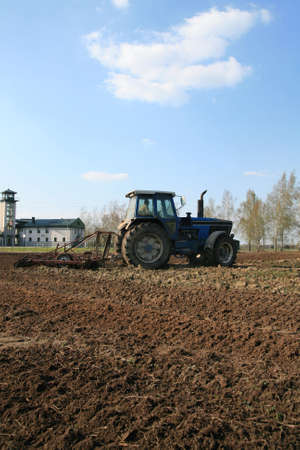 Farmers plowing with tractor in agricultural field Stock Photo