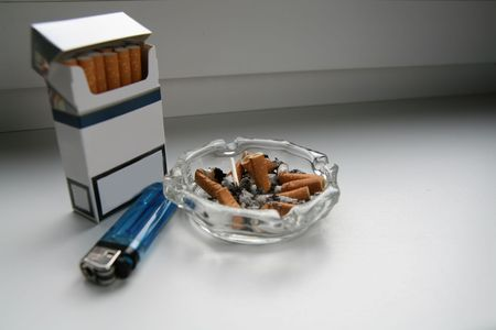 Cigarette pack, cigarette-lighter and ashtray with cigarette butts... or stud to heart! photo