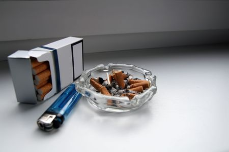 Cigarette pack, cigarette-lighter and ashtray with cigarette butts... or stud to ! photo