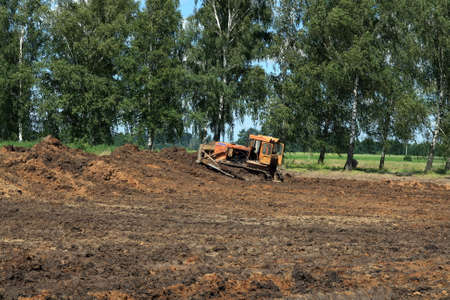 Bulldozer shaping hill for new house