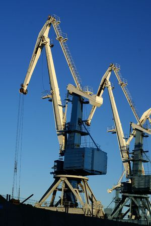 stowing: Image of an industrial port large cranes against blue sky