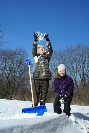 mother and daughter shoveling and have fan outside Stock Photo - 2785177