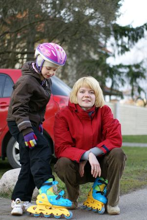 Mother helping her dauther to dress rollerblades       photo