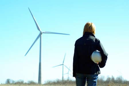 desarrollo sustentable: Mujer ingeniero o arquitecto con sombrero blanco de seguridad y las turbinas e�licas a fondo