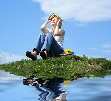 female student outdoor on green grass with books and blue sky on background and reflection photo
