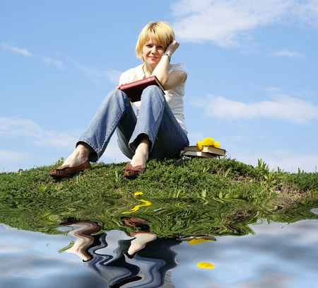 female student outdoor on green grass with books and blue sky on background and reflection Stock Photo - 3041573