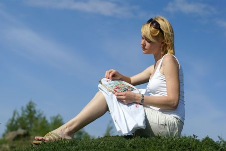 counted: woman cross-stitching in the park with blue sky on background  Stock Photo