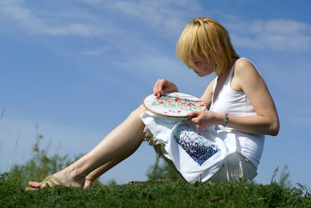 counted: woman cross-stitching in the park with blue sky on background