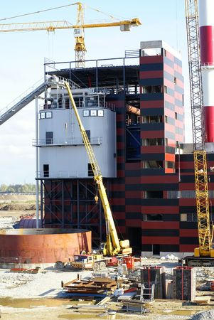 cranes and chimney on construction of industrial factory            photo