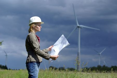 windy energy: Woman engineer or architect with white safety hat and wind turbines on background