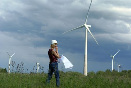 Woman engineer or architect with white safety hat and wind turbines on background   Stock Photo
