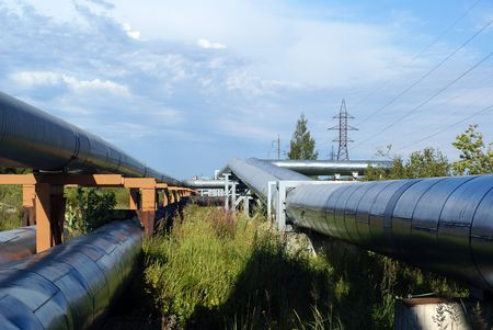 volts: industrial pipelines on pipe-bridge and electric power lines  against blue sky                      Stock Photo