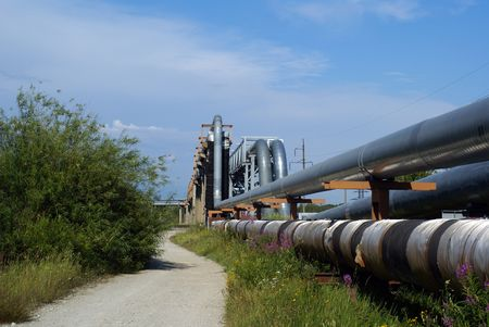 volts: industrial pipelines on pipe-bridge and electric power lines  against blue sky