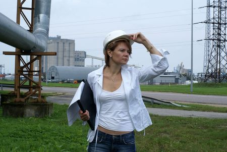 Woman engineer or architect with white safety hat, drawings and industrial pipelines on background              photo