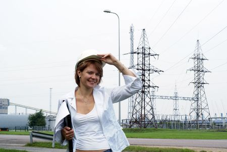 Woman engineer or architect with white safety hat drawings and electrical towers structure on background           photo