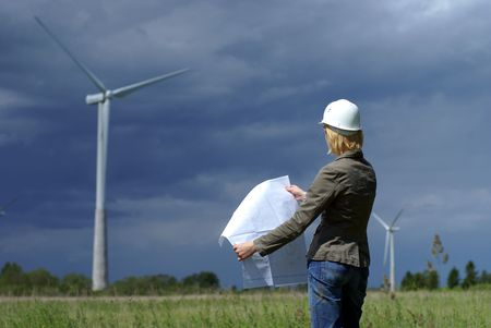 windy energy: Woman engineer or architect with white safety hat and wind turbines on background          Stock Photo