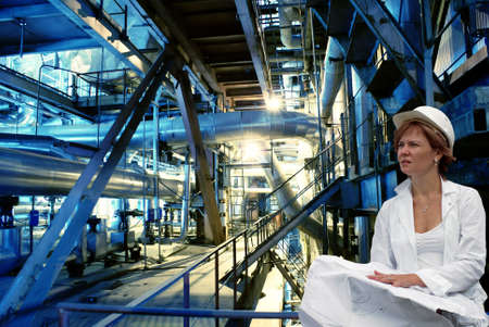 woman engineer, pipes, tubes, machinery and steam turbine at a power plant                  Stock Photo