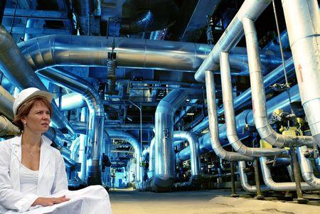 turbina de vapor: mujer ingeniero, tuber�as, tubos, maquinaria y turbina de vapor en una planta de energ�a Foto de archivo