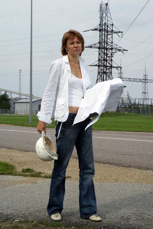 tired woman engineer or architect with white safety hat drawings and electrical towers structure on background      photo