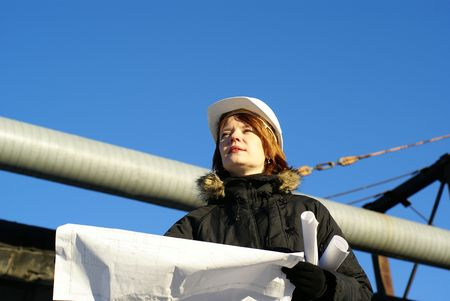 Young architect looking at blueprint in front of construction site against blue sky             photo