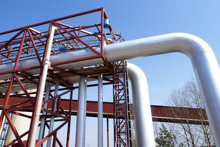 immense: industrial pipelines on pipe-bridge against blue sky                 Stock Photo