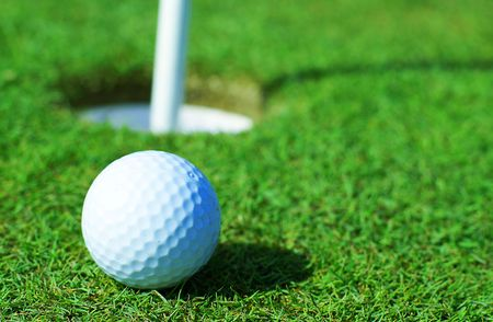 Golfball in front of the hole            photo