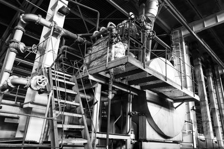 Equipment, cables and piping as found inside of a modern industrial power plant b&w                    photo