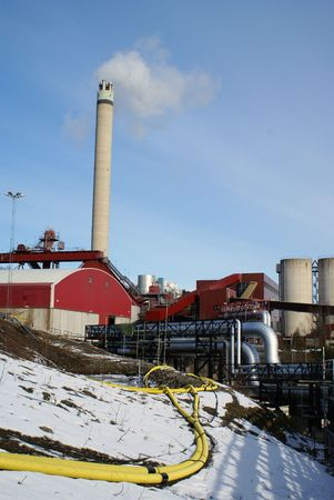 industrial pipelines and smoke stack against blue sky                photo