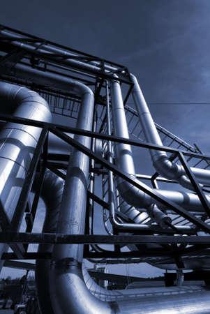 refiner�a de petr�leo: Tuber�as, pernos, v�lvulas contra un cielo azul en tonos de azules