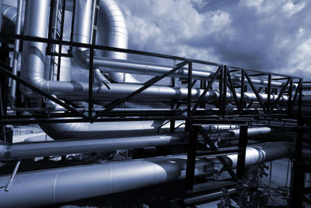 refineries: Pipes, bolts, valves against blue sky in blue tones