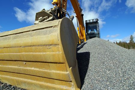Hydraulic excavator at work. Shovel bucket against blue sky                 photo