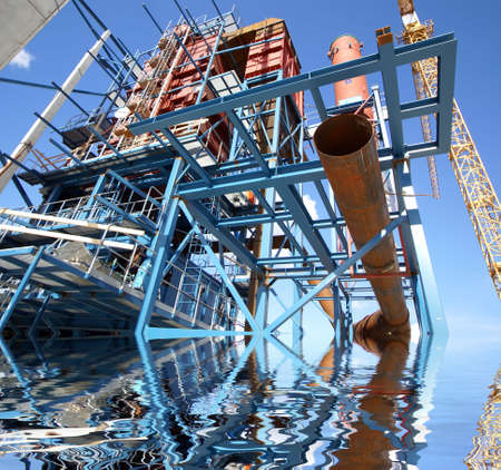 steel blue: cranes and beams on construction of industrial factory with reflection
