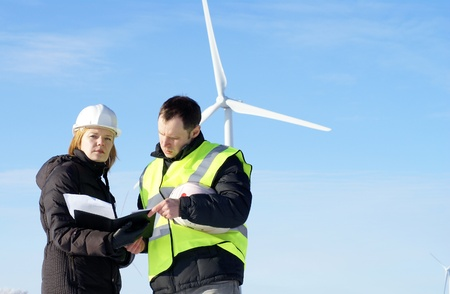 team of  engineers or architects with white safety hat and wind turbines on background photo