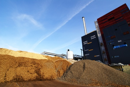 biomasa: planta de energ�a con el almacenamiento de combustible de madera contra el cielo azul