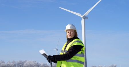 engineer or architect with white safety hat and wind turbines on background photo