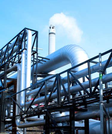 turbina de vapor: ductos industriales y chimeneas con un fondo azul natural Foto de archivo