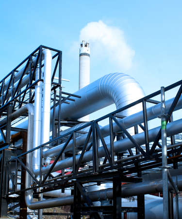 steam turbine: industrial pipelines and smokestack with a natural blue background