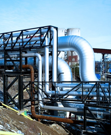 oil pipeline: industrial pipelines with insulation against natural blue background Stock Photo