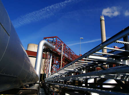 Industrial zone, Steel pipelines and smokestack on blue sky                  photo