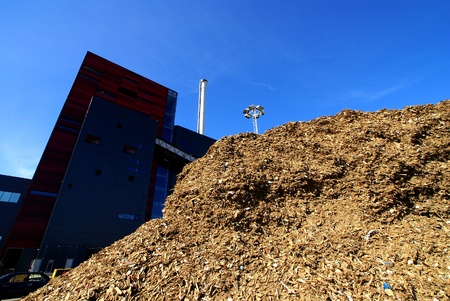 bio power plant with storage of wooden fuel against blue sky  photo