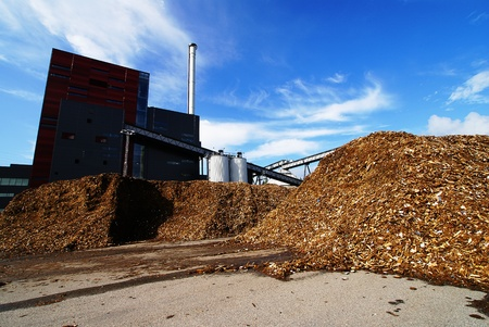 anaerobic: bio power plant with storage of wooden fuel against blue sky